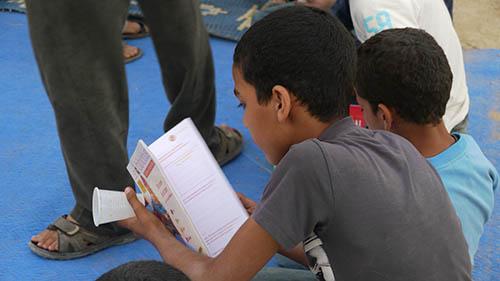 enfant lisant lors d'un projet d'art de rue Nawak Production
