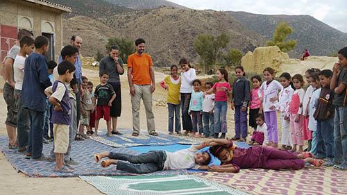 groupe d'enfants et d'adultes autour d'une démonstration d'art de rue projet Nawak Production