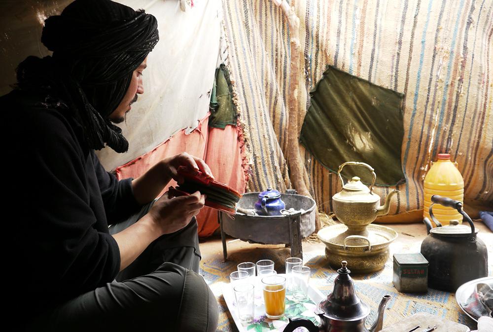 Un homme prépare le thé marocain lors du séjour méharée dans le désert en famille