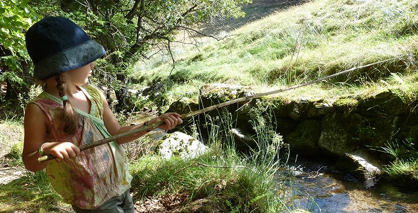 petit fille pêchant avec un bâton lors d'un séjour jeunesse Azimut Voyage