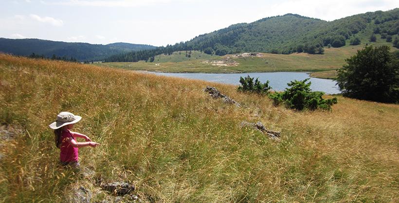petite fille au milieu d'un champ près d'un lac lors d'un séjour jeunesse azimut voyage