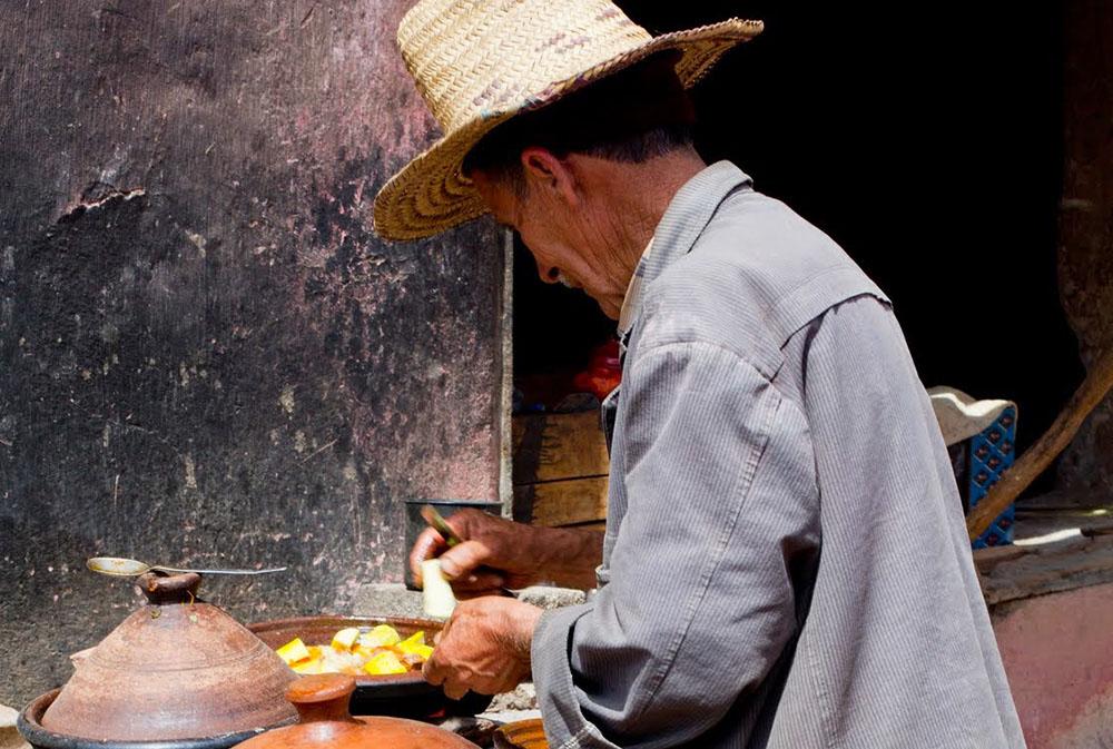 Un homme prépare un Tajine lors des rencontres avec les Berbères