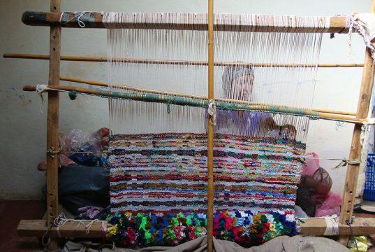Une femme tisse un tapis coloré lors du séjour rencontre avec les Berbères