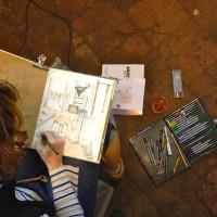 Photo prise d'en haut d'une voyageuse en train de croquer, on peut observer son carnet sur lequel elle est en train de dessiner et sa boite à crayons multicolores à sa droite