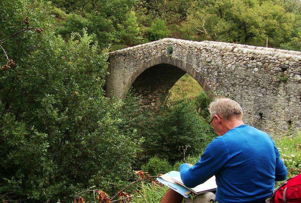 Un dessineteur croque un vieux pont tout en pierre situé non loin du beau village de caractère d'Aumessas