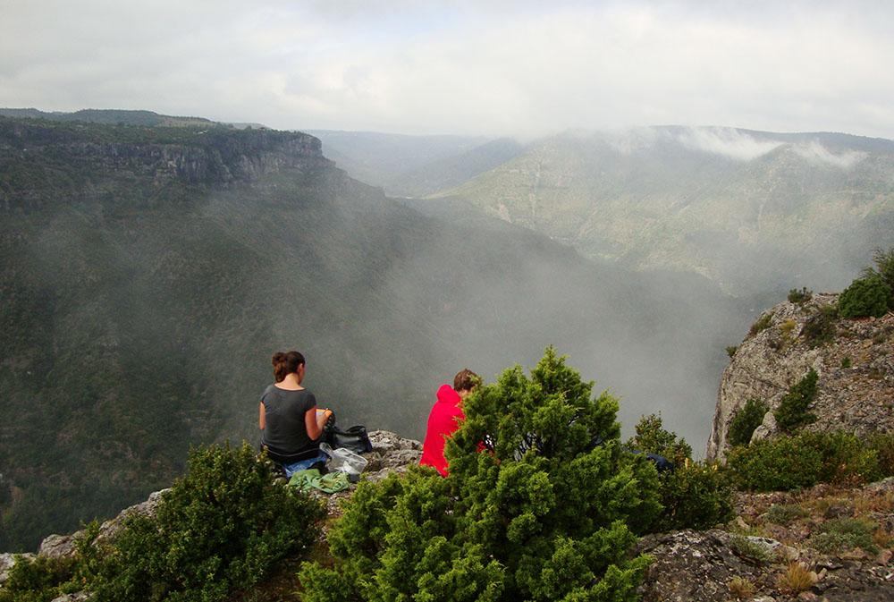Deux dessinatrices sont assises en pleine nature non loin du cirque de Navacceles avec une superbe vue entourée de brouillard sur les gorges