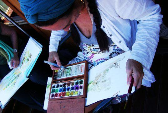 Voyageuse en train de dessiner sur un bateau le long du Douro