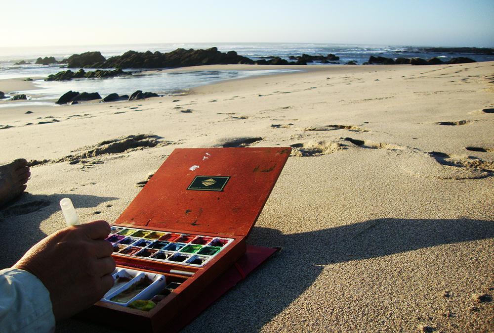 Palette d'aquarelle posée sur le sable au bord de l'océan au Portugal