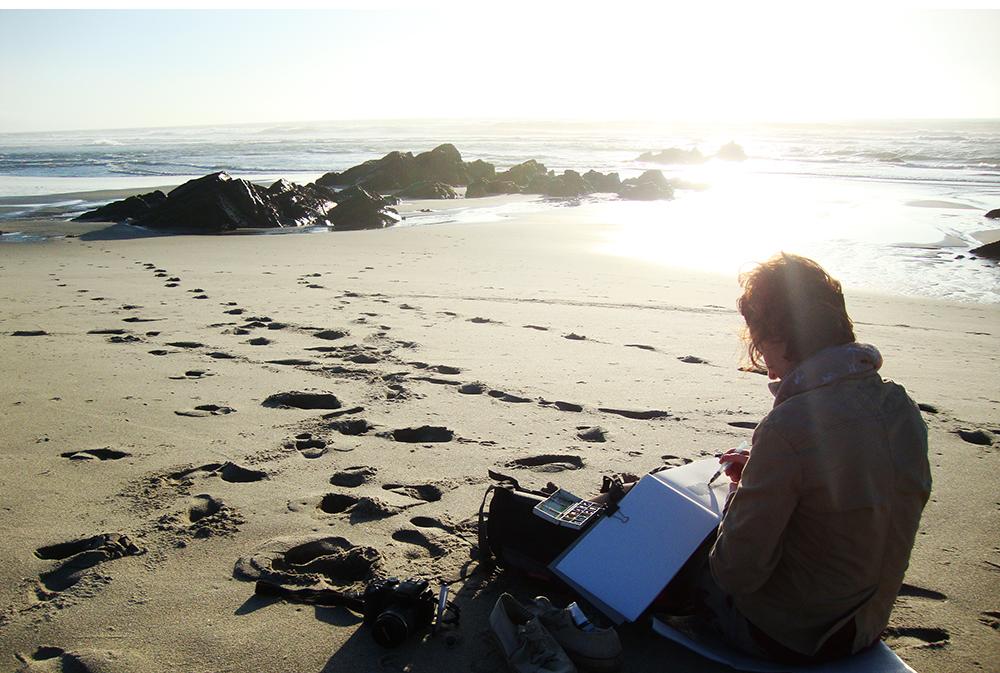 Voyageuse en train de croquer sur une grande plage au bord de l'océan