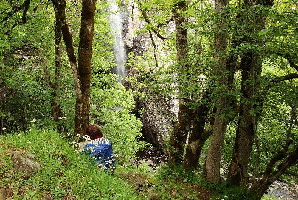 Une voyageuse en train de dessiner la cascade du Déroc sur l'Aubrac