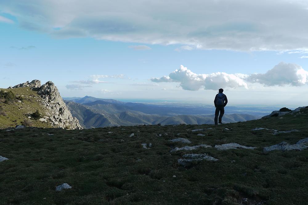 Randonnée dans les Pyrénées, Paul observe depuis les contreforts des Pyrénées la mer